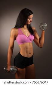 Beautuful hispanic woman workout with dumbbells studio portrait