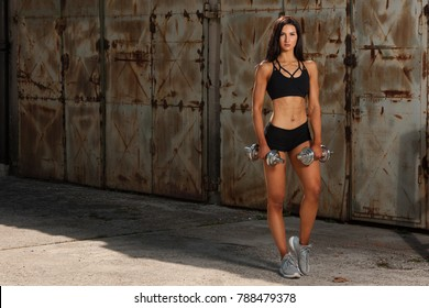 Beautuful hispanic woman workout with dumbbells studio portrait