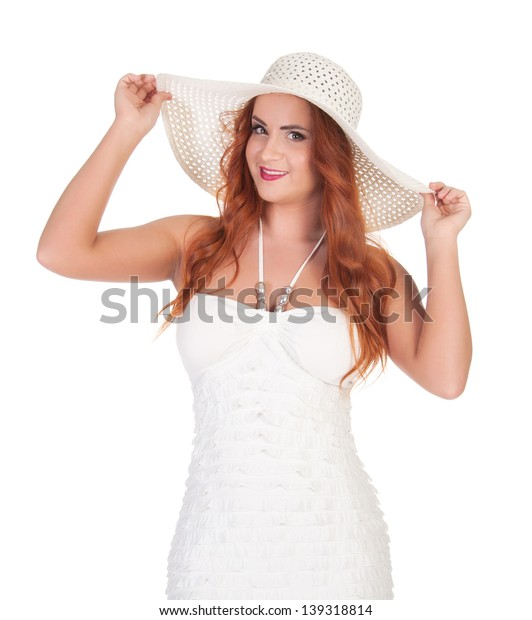 Beautuful woman with red long hair posing in white dress and hat. over white background