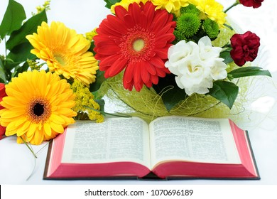 Beaututiful flowers with open Bible on white background