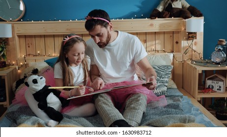 Beauty affectionate family portrait. Close-up zoom in view happy handsome dad and his daughter dressed like fairies reading a book together while sitting in bedroom. Home party.