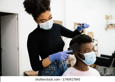 Beauty African-American hairdresser peeling and combing an African-American male client both wearing a face mask and gloves to protect himself from the coronavirus pandemic - Shutterstock ID 1740927845