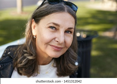 Beauty, aging, maturity, style and fashion concept. Close up portrait of carefree beautiful middle aged female pensioner in stylish clothes relaxing outdoors in park, her look full of wisdom and joy
