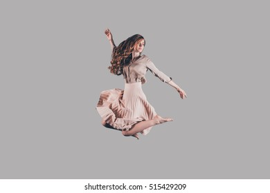 Beauty in the air. Studio shot of attractive young woman hovering in air