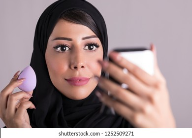 Beauty Arab woaman applying makeup.  looking in the mirror and applying cosmetic powder with a brush. skin care