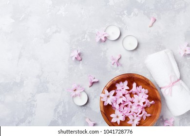 Beauty, aromatherapy and spa background with perfumed pink flowers water in wooden bowl and candles on stone table. Top view, flat lay.