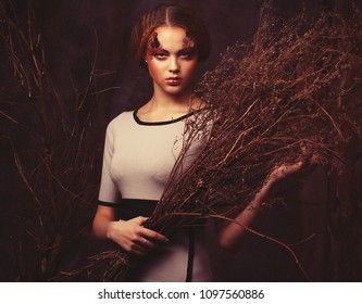 Beauty and art concept: Young woman with bright make up with dry branches, studio shoot