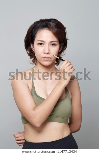 A beauty asian girl applying makeup on the grey background, Portrait of young woman in beauty saloon interior. Applying tone to skin.