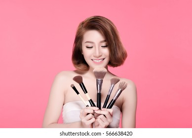 Beauty Asian Girl with Cosmetics Set. She so happy smiling and holding powder brush collection, Natural makeup with beautiful v-shape face and short hair style.