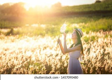 Beauty Asian Girl Outdoors enjoying nature. Beautiful Teenage Model girl in white dress running on the Spring Field, Sun Light.