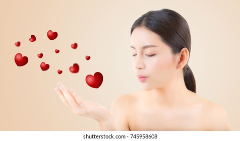 Beauty asian woman blowing mouth valentine heart with perfect make up, Girl showing love. Gestures for advertising cosmetic on yellow background.