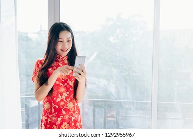 Beauty Asian Woman with Chinese dress,Qipao,Cheongsam Chinese New Year Using Smartphone Technology Shopping Online Standing near Window in Clean White Room,Copy Space.