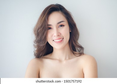 Beauty Asian Woman face Portrait. Beautiful Spa model Girl with Perfect Fresh Clean Skin. Blonde female looking at camera and smiling. Youth and Skin Care Concept