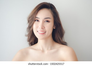 Beauty Asian Woman face Portrait. Beautiful Spa model Girl with Perfect Fresh Clean Skin. Blonde female looking at camera and smiling