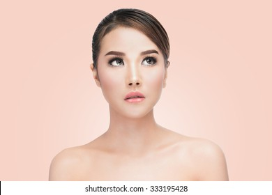 Beauty Asian Woman face Portrait. Beautiful Spa model Girl with Perfect Fresh Clean Skin. looking up. Youth and Skin Care Concept. on pink background with clipping path