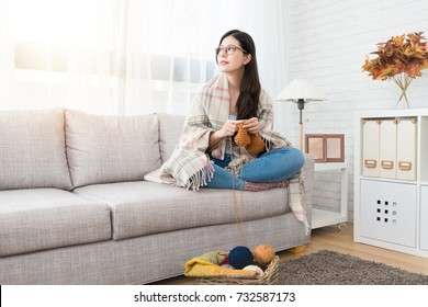 beauty asian woman keeping warm by put the blanket on top and looking outside view and knitting on the sofa in the living room at home