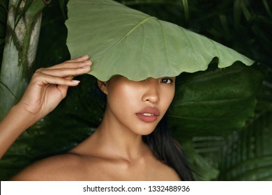 Beauty. Asian woman model with green leaf over face. Portrait of exotic girl with natural skin and sexy big lips covering head with plant in tropical nature