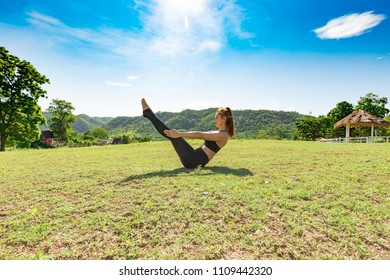 Beauty Asian woman practice yoga boat pose or Navasana pose stretching exercise muscle with yoga meditation relax and refresh health on green grass feeling happiness and comfortable,Healthcare Concept
