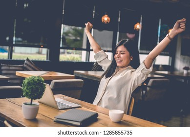 Beauty Asian woman raising two hands after finishing job happily with laptop computer. People and lifestyles concept. Technology and Business working theme. Occupation and coffee shop theme.