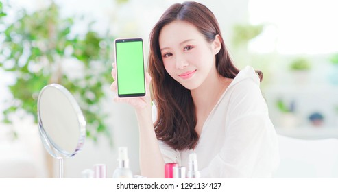 Beauty asian woman show smart phone with skin care products at home