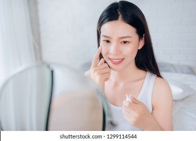 Beauty Asian Woman use Acne Gel Skincare after Cleansing on Face His Happiness and Look at mirror in White Bedroom.