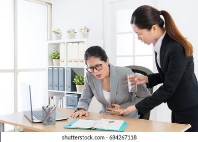 beauty attractive woman leader getting gastroenteritis illness feeling painful and young pretty female assistant giving her treatment pill.