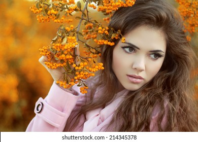 Beauty autumn portrait of attractive girl over yellow brunch of seasonal park
