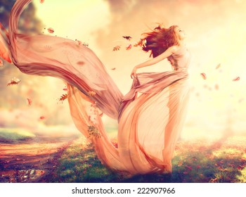 Beauty Autumn Woman, beautiful fantasy girl, fairy in blowing transparent chiffon dress. Fall. Fashion model lady in windy autumn park