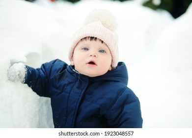 Beauty baby girl in warm snowsuit and pink hat walking and playing in the backyard in snow