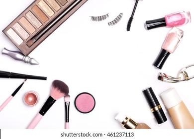 Beauty background concept, idea for cosmetics make up objects: lipstick, nail polish, eye shadows, false eyelashes, brush and mascara with space for text isolated on white background.