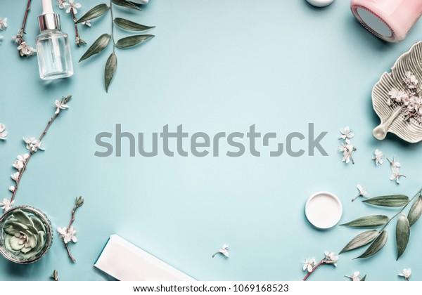 パステル青のデスクトップ背景に美しい背景と、美しい化粧品、葉、桜。現代の春のスキンケアのレイアウト、上面、平らなレイ。