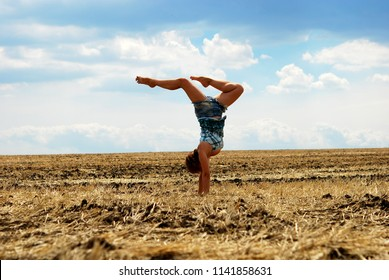 Beauty Ballerina Girl Outdoors enjoying nature. Dancer jumping on summer field. Sun Light. Free Happy Woman. happy girl running jumping carefree with outstretched hands over yellow field gray blue sky