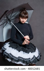 beauty ballerina with silver umbrella on grey background