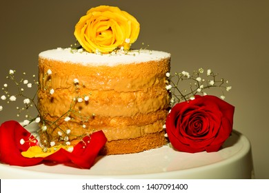 Beauty And The Beast. Naked cake of well-married with warm colors. Nude cake of well-married with milk sweet filling decorated with red and yellow roses and mosquito flowers
