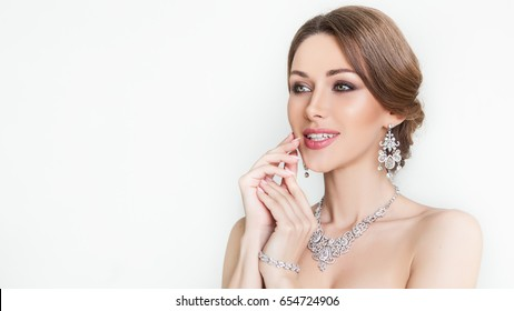 Beauty. Beautiful bride. Wedding hairstyle and make up. Portrait wedding makeup and hairstyle, girl in diamonds, jewelry model, fashion bride gorgeous beauty, smiling happy bride woman. Earrings