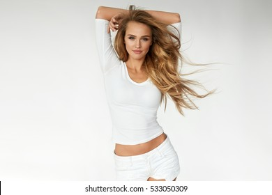 Beauty. Beautiful Woman With Perfect Long Blonde Wavy, Curly Hair Standing On White Background. Portrait Of Happy Girl With Fit Sexy Body And Natural Face Makeup. Health Concept. High Resolution