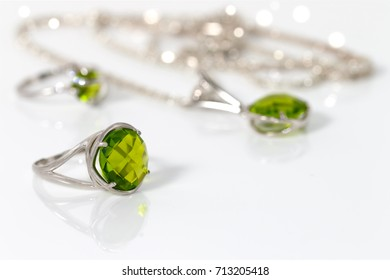 Beauty big silver ring with peridot on background pendant and small  ring on white acrylic desk.