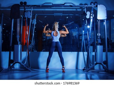 Beauty bikini model pumps arm muscles in gym