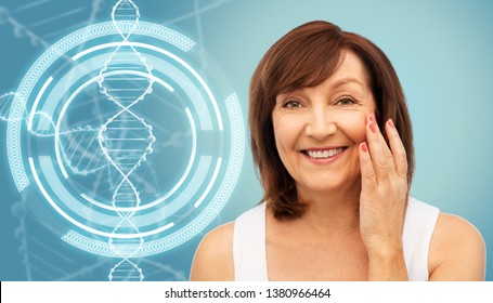 beauty, biotechnology and anti-age concept - portrait of smiling senior woman touching her face over blue background and dna molecule hologram