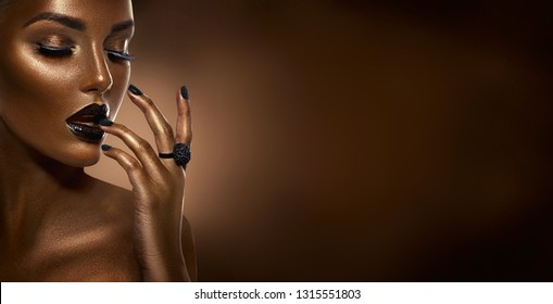 Beauty Black girl fashion art portrait over dark brown background. Professional make-up and manicure. Sexy Afro American young woman with beautiful skin. Chocolate. Black nails and lipstick