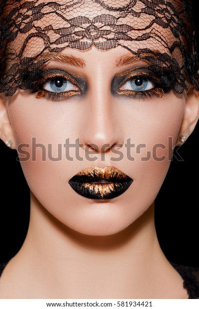 Beauty Black and gold Makeup Detail. avant-garde make-up using mother-of-pearl shades and shine, black lips and eyes covered with gold loose. Kiss.Close-up Beauty Model   Woman's Face Make-up