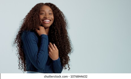 Beauty black mixed race african american woman with long curly hair and perfect smile looking at camera and smiling on blue