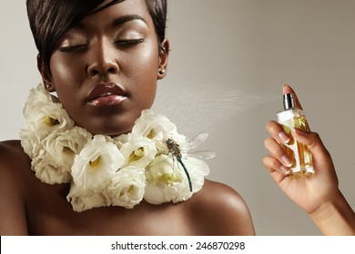 beauty black woman with flowers on her neck and a hand with a perfume bottle