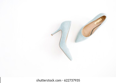 Beauty blog concept. Pale blue female shoes on white background. Flat lay, top view trendy fashion feminine background.
