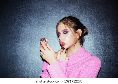 Beauty bloger. Girl with lipstick on lips. girl use phone as mirror. put lipgloss. Fashion portrait of woman. Makeup cosmetics and skincare. woman with fashion makeup. Beauty salon. Facial care.