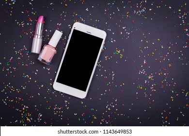 Beauty blogger concept. Smartphone, lipstick and nail polish on black sprinkled background. Flat lay, closeup, no retouch, copy space.