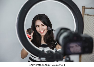 beauty blogger. makeup tutorial. video blog concept. portrait of asian woman showing makeup tutorial online using camera and lighting equipment