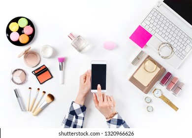 Beauty blogger with smartphone and makeup cosmetics on white background