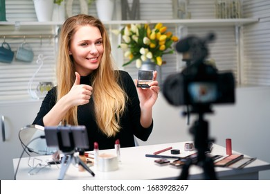 Beauty blogger woman filming daily make-up routine tutorial near camera. Influencer girl live streaming cosmetics product review. Vlogger female recommends eye shadow palette showing thump up sign.
