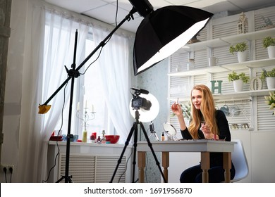 Beauty blogger woman filming daily make-up routine tutorial on camera. Influencer blonde girl live streaming cosmetics product review in home studio with professional lighting equipment. Vlogger job. - Shutterstock ID 1691956870